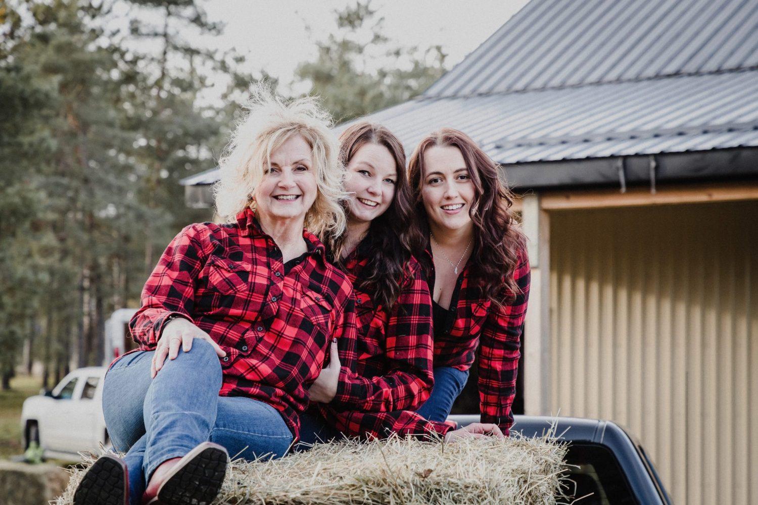 mom and daughters sitting on a hay bale on a farm in ontario for a family photography session by cobourg family photographer heather doughty photography