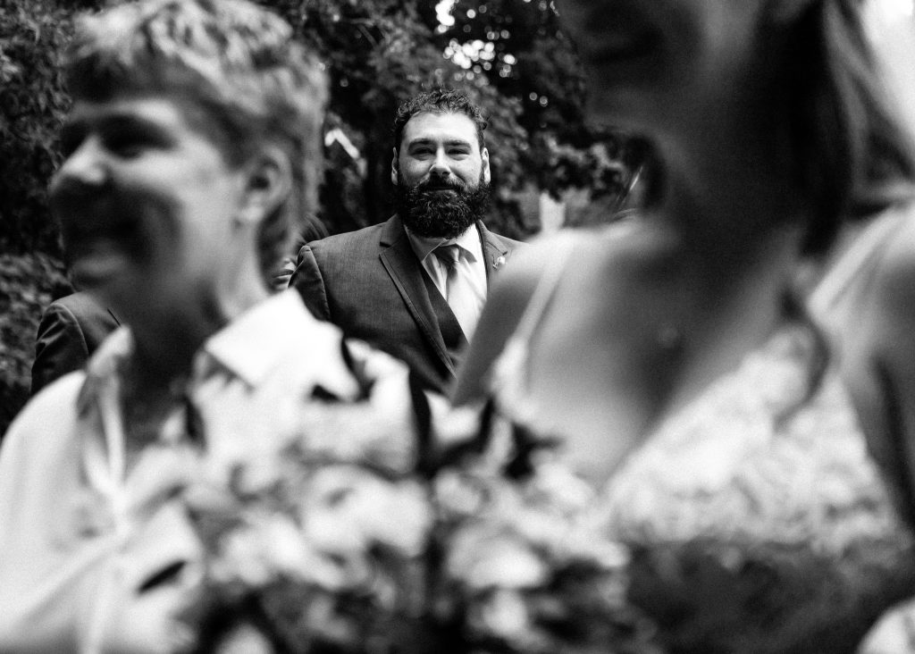 intimate home wedding as bride walks down the aisle with her brother looking on photographed by intimate wedding photographer heather doughty photography
