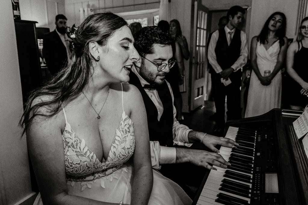 bride and groom singing and playing the piano at their home wedding for their wedding guests photographed by intimate wedding photographer heather doughty photography