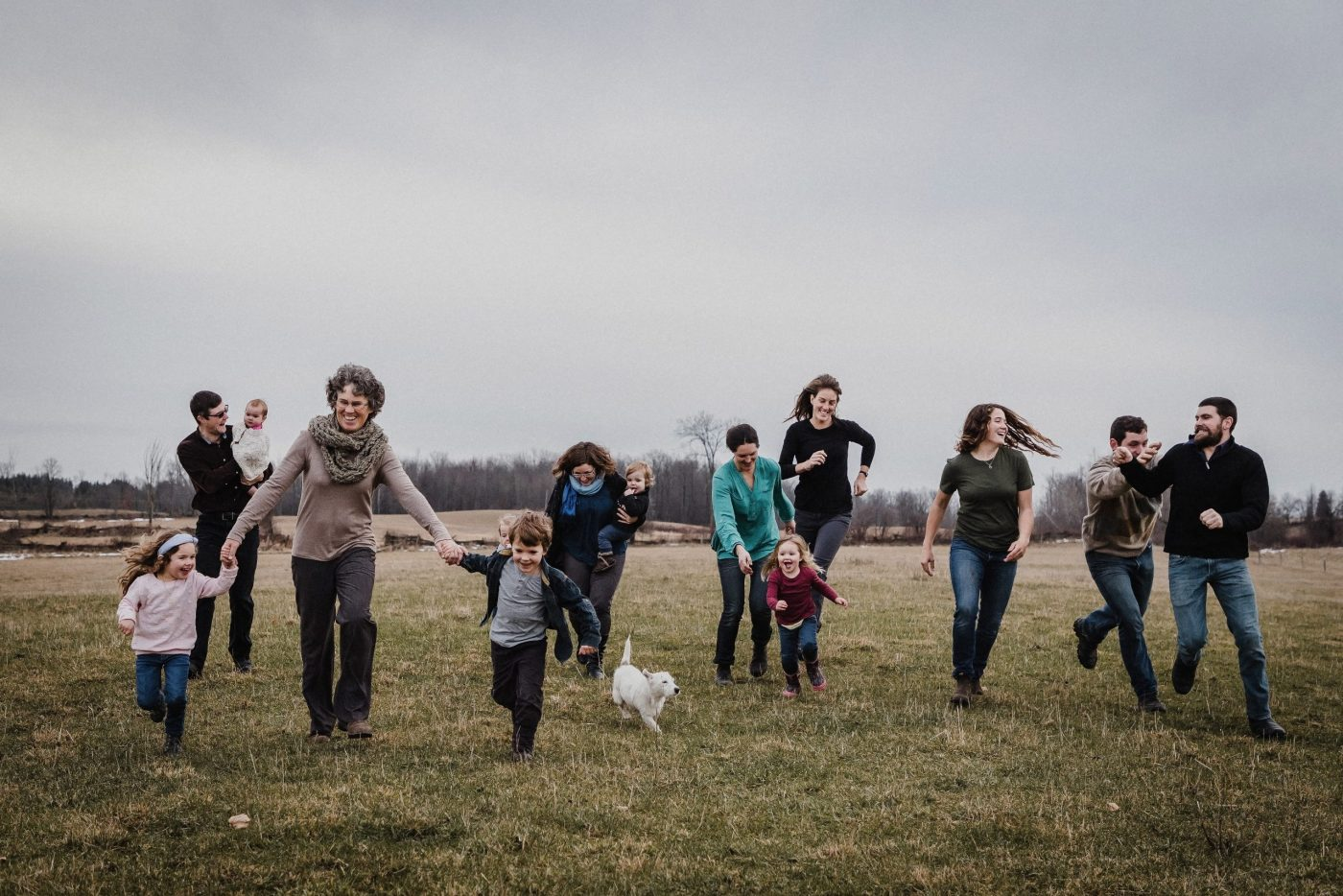 family running through farm field in ontario for family photo session by family photographer heather doughty photography