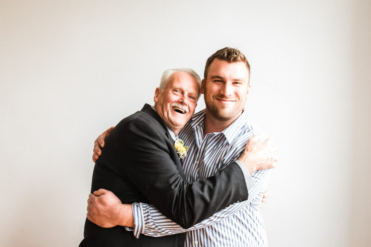 grandfather and grandson hugging and laughing in photography studio in downtown peterborough ontario for 50th wedding anniversary family photo session by ontario family photographer heather doughty photography
