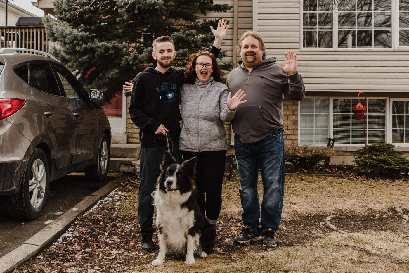 mother, father, son and border collie on front lawn of a house in the surburbs of peterborough, ontario waving for a family photography session by heather doughty photography