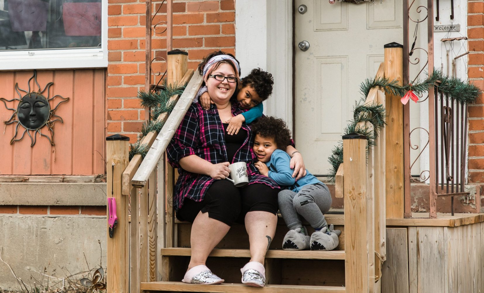 mother and two boys sitting on porch steps of a house in peterborough ontario during covid 19 pandemic for family session by ontario portrait photographer heather doughty photography