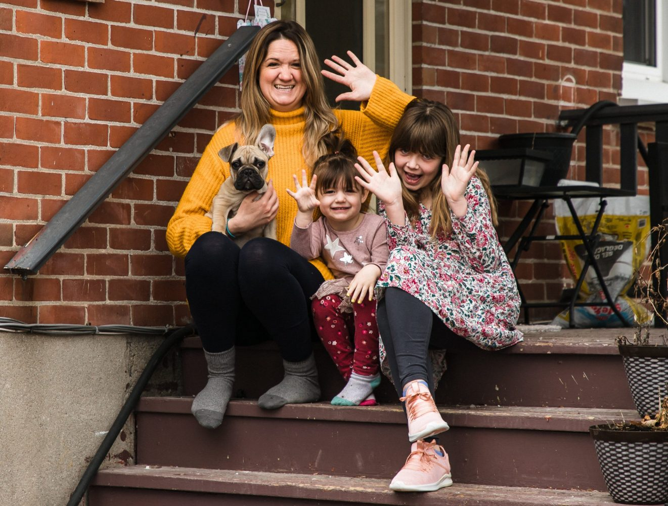 mom and daughters sitting on porch in city, waving at family photographer for family session