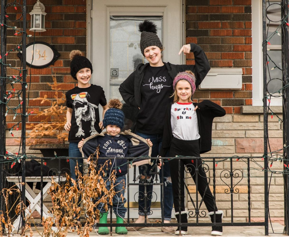 mom and kids standing on porch during covid 19 posing for family photo session by ontario family photographer heather doughty photography