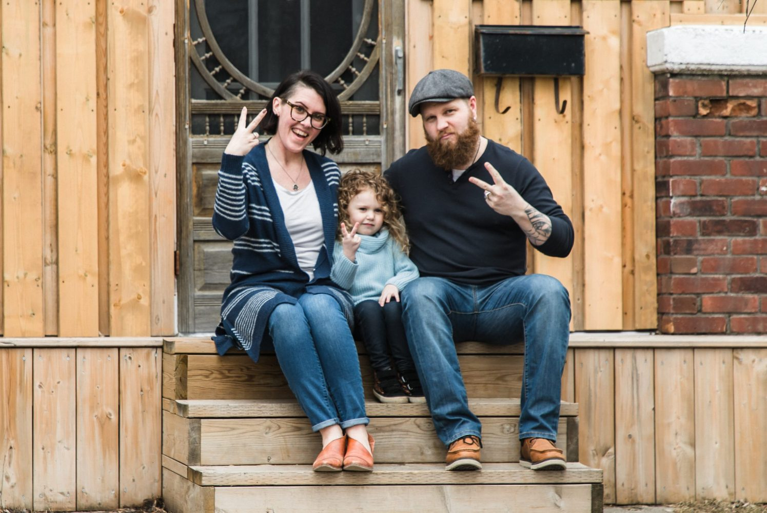 family sitting on front porch step for family session by peterborough ontario family photographer heather doughty photography