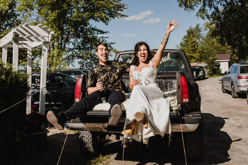 wedding couple leaving their wedding in the back of a pick up truck, yelling and cheering at their house wedding in cobourg, ontario