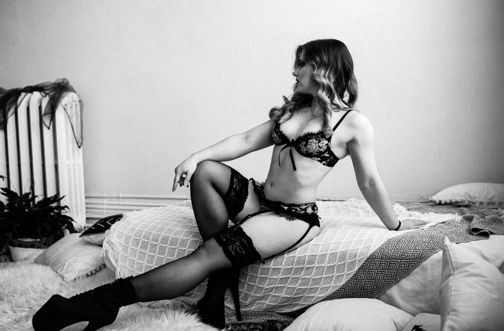 Woman reclining on bed during body positive boudoir session in Peterborough