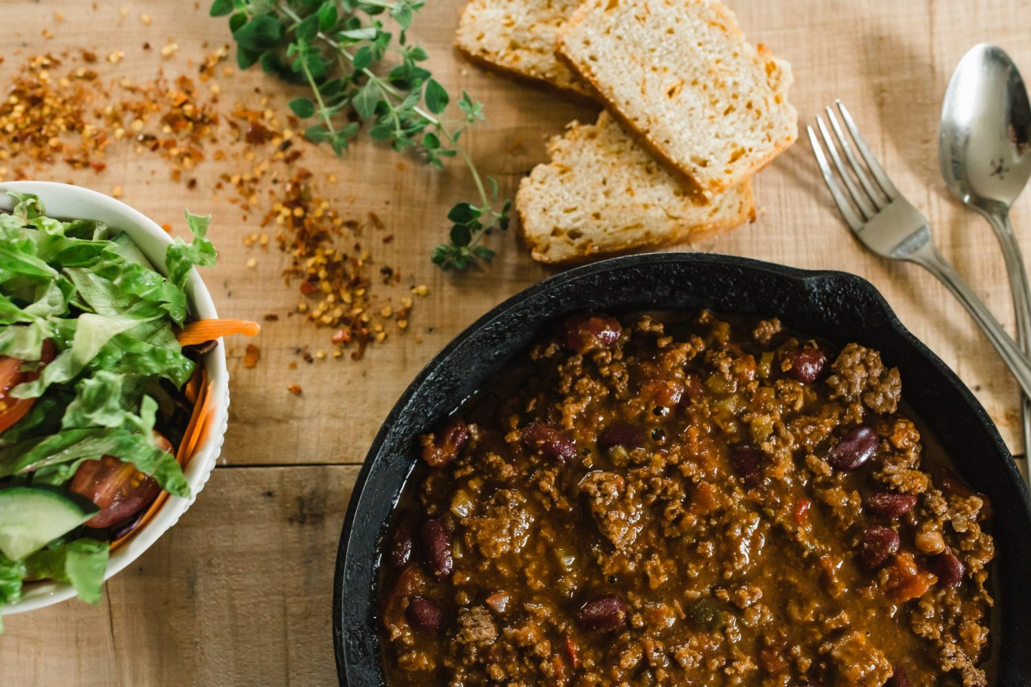 beef chili in cast iron frying pan with garden salad from thats a wrap catering in peterborough ontario by ontario food photographer heather doughty photography