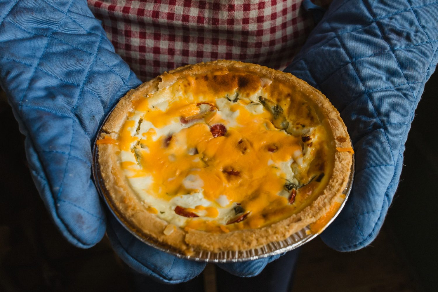 comfort food ham and cheese quiche just out of the oven being held by ovenmittens by peterborough food photographer heather doughty photography