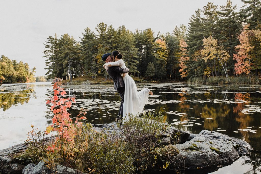 groom lifting bride up on a rock by the water for their couple portraits at their intimate cottage elopement