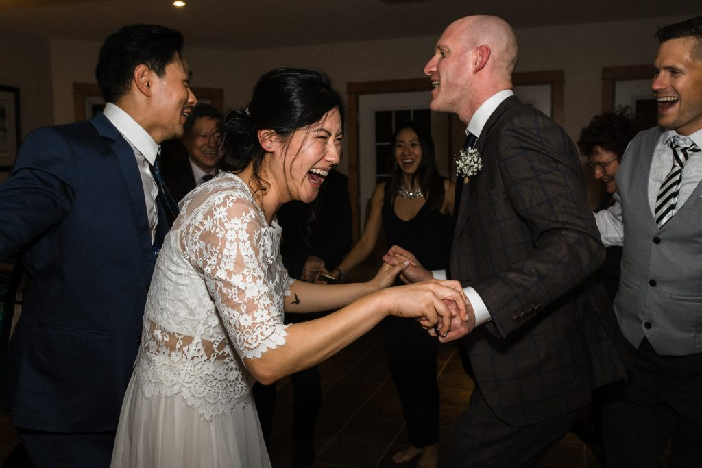 wedding couple laughing with bride sitting on grooms knee at their intimate elopement wedding