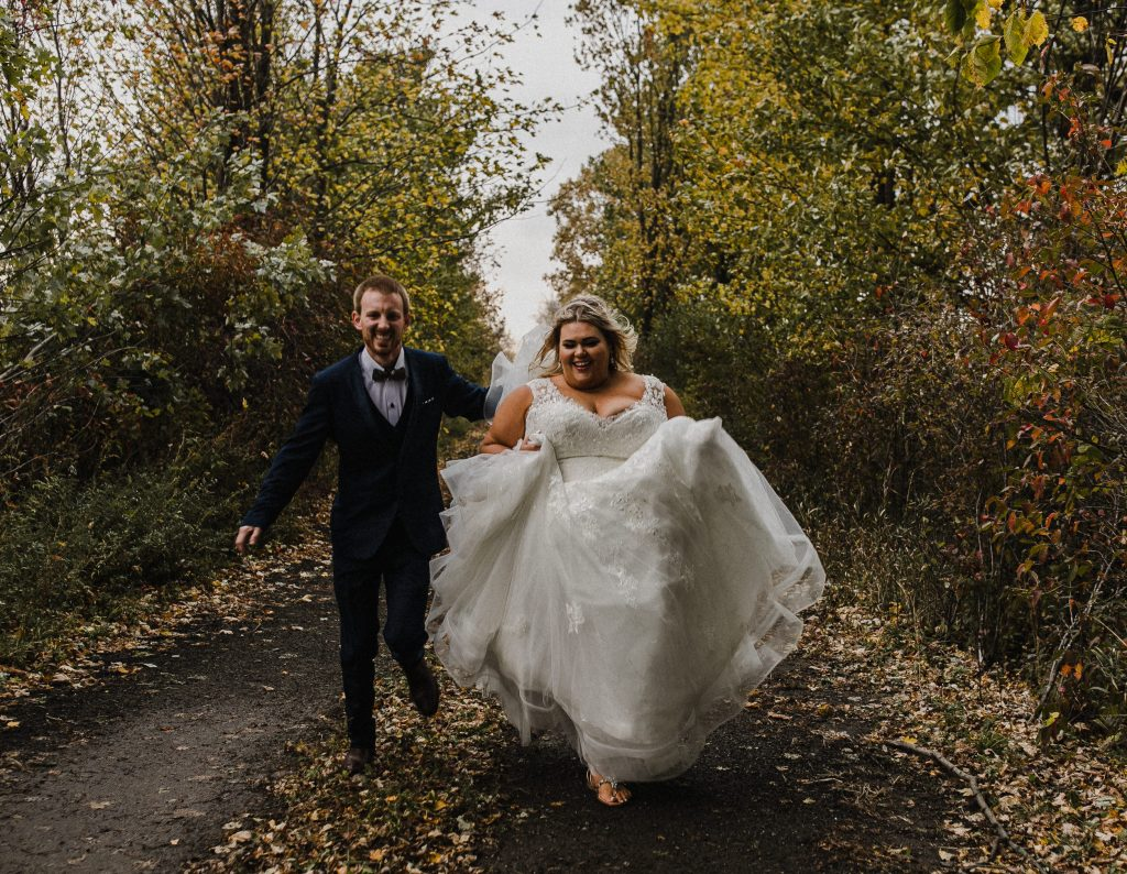 wedding couple running down a laneway in the fall at their intimate home wedding in ottawa