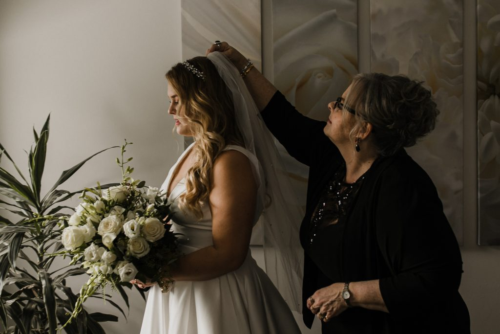 bride and mother of the bride standing together as mother of the bride puts the bride's veil in her hair at the wedding couples intimate home wedding