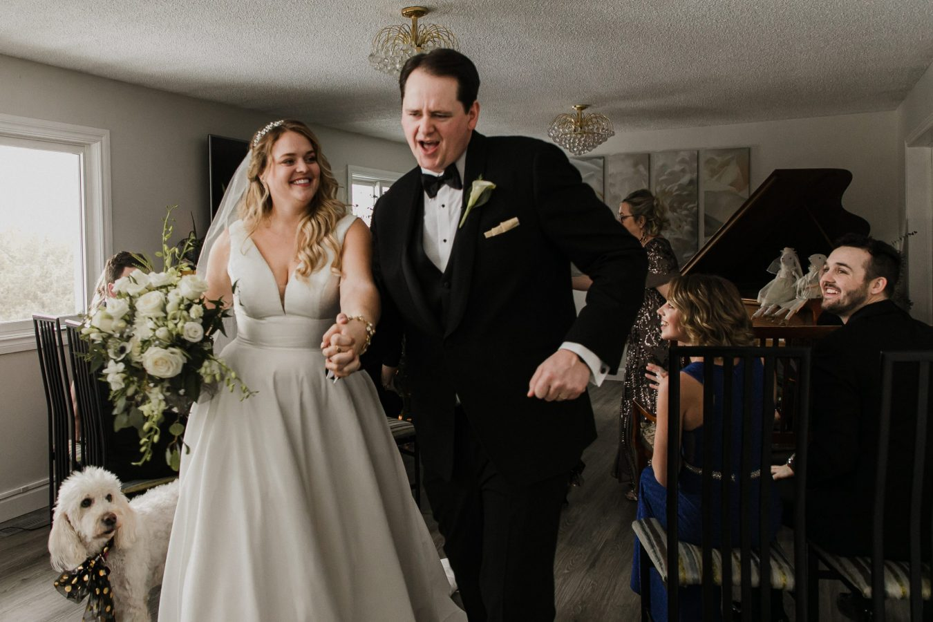 bride and groom dancing down the aisle after getting married at their intimate home wedding