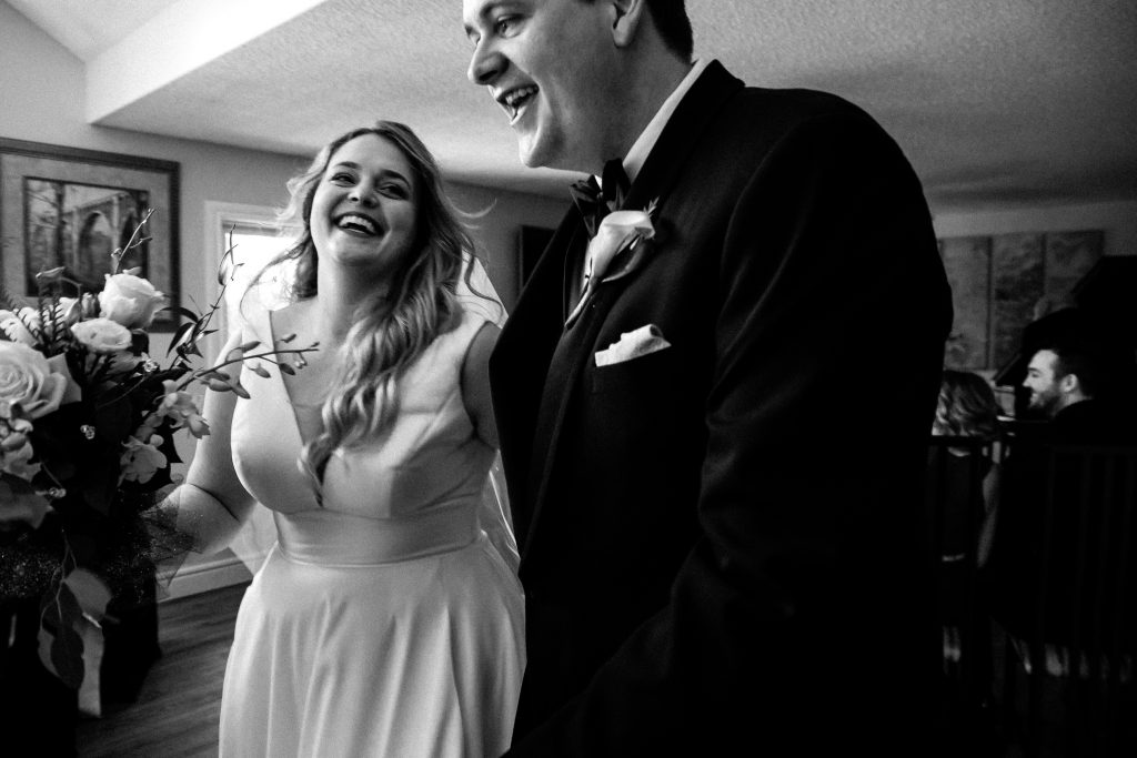 wedding couple singing and dancing down the aisle after being married in an intimate home wedding in cobourg