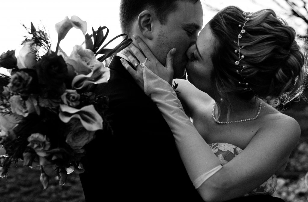black and white close up portrait of bride and groom kissing on their wedding day at their intimate micro wedding