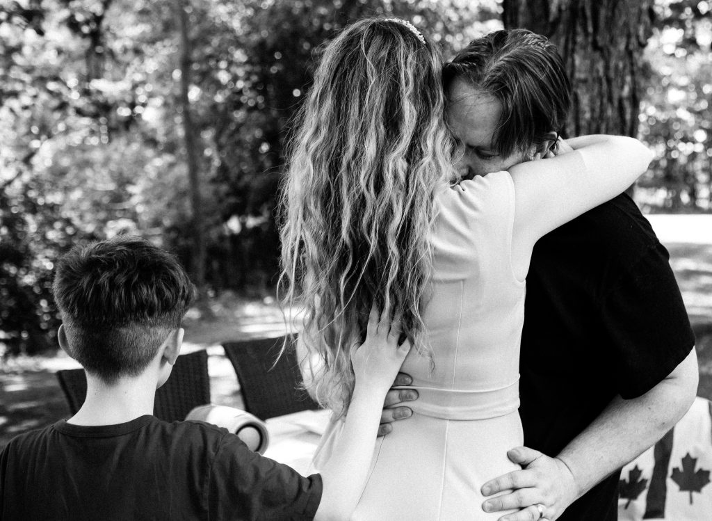 wedding couple hugging just after being declared husband and wife at an outdoor intimate elopement home wedding in Fenelon Falls